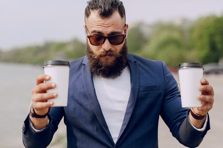 bearded man carrying coffee on hot summer day