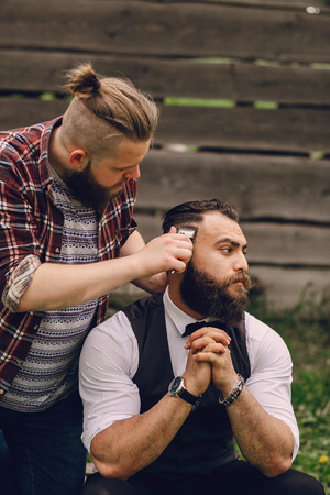 cut off head: two bearded men shave outdors on summer day