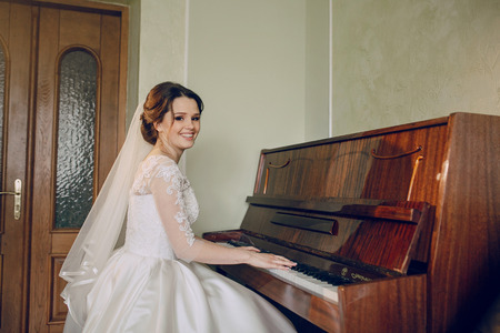 beautiful bride is sitting at the piano