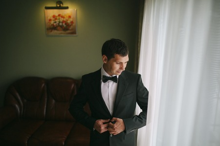 bata blanca: la ma�ana de la boda el novio de cocina elegante con un traje Foto de archivo