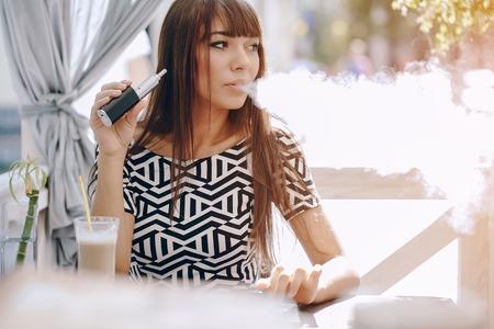 beautiful brunette smoke electronic cigarette on the summer terrace of restaurant