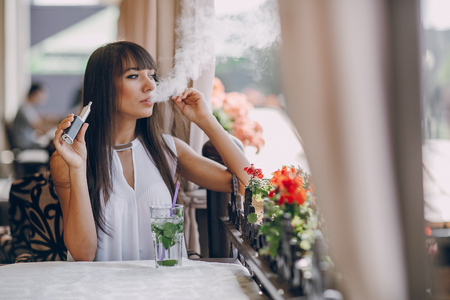 beautiful brunette smoke electronic cigarette on the summer terrace of restaurant