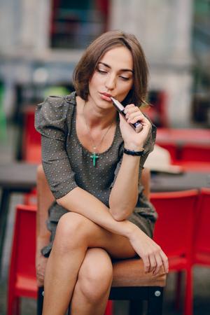 Bella bruna fumo di sigaretta elettronica sulla terrazza estiva del ristorante Archivio Fotografico - 45708409