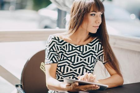 Pretty Girl met behulp van tablet telefoon in cafe