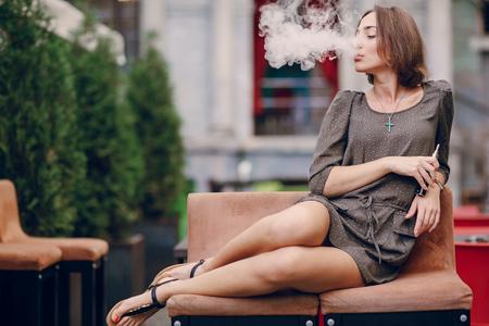 Bella bruna fumo di sigaretta elettronica sulla terrazza estiva del ristorante Archivio Fotografico - 45708416