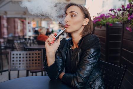 mooie sexy brunette vrouw in een cafe in een lederen jas
