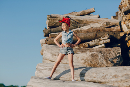 happines: little girl sitting on the wood style pin up in jeans clothes Stock Photo
