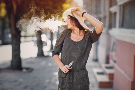 beautiful brunette smoke electronic cigarette in public places
