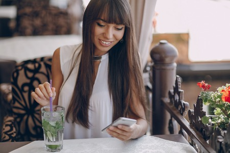 lady on phone: beautiful girl using telephone and drinking mojitos Stock Photo