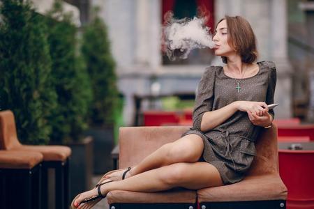 finger on lips: beautiful brunette smoke electronic cigarette on the summer terrace of restaurant