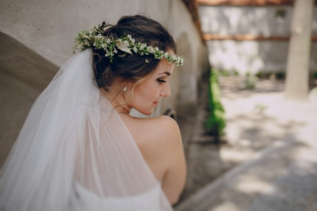 nude bride: bride poses for photos in wedding dress and wreath