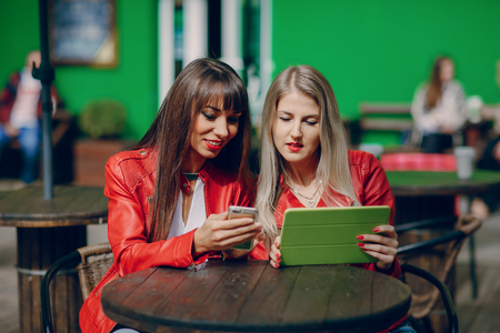 two beautiful girls photographed with gadgets and walk city Stock Photo