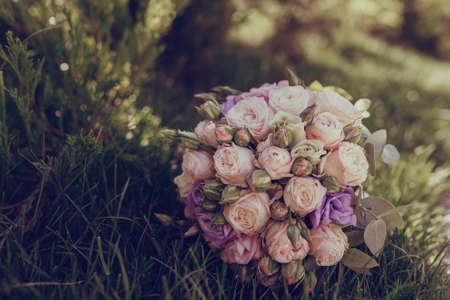 position d amour: beautiful wedding bouquet on a sunny day lying on the grass
