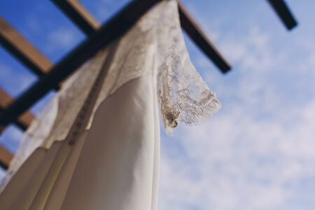 summer dress: gorgeous wedding dress hanging outside on a sunny day
