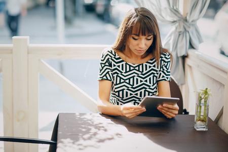 Pretty Girl con telefono tablet nel caffè Archivio Fotografico - 49500012