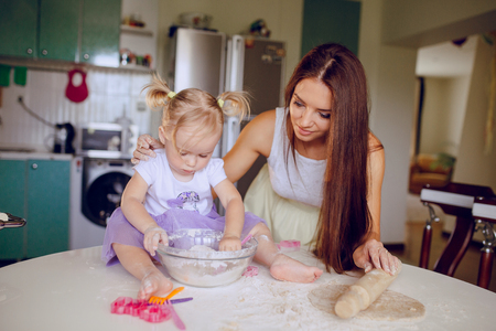 teaches: young beautiful mother teaches daughter prepare dough in the kitchen Stock Photo