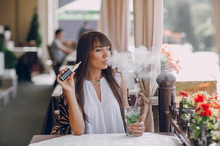 Bella bruna fumo di sigaretta elettronica sulla terrazza estiva del ristorante Archivio Fotografico - 50880362