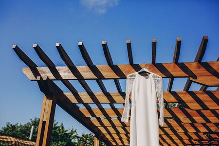 elegant dress: gorgeous wedding dress hanging outside on a sunny day