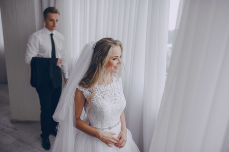 brunette hair: beautiful blonde bride preparing for her wedding with groom