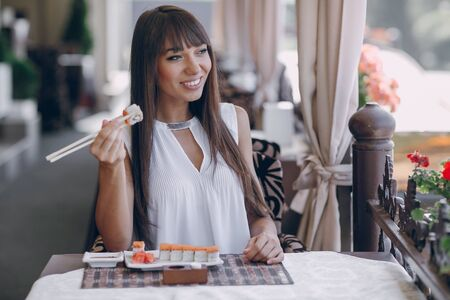 beautiful girl enjoying sushi in a cafe on a sunny day Stock Photo
