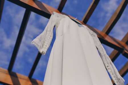woman dress: gorgeous wedding dress hanging outside on a sunny day