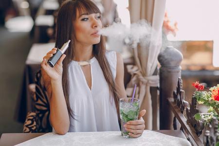 Bella bruna fumo di sigaretta elettronica sulla terrazza estiva del ristorante Archivio Fotografico - 54512613