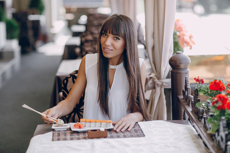 eating dinner: beautiful girl enjoying sushi in a cafe on a sunny day Stock Photo