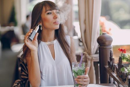Bella bruna fumo di sigaretta elettronica sulla terrazza estiva del ristorante Archivio Fotografico - 55185404
