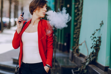 spectacular young brunette outside uses fashionable and healthy e-cigarette Banque d'images