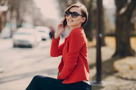 young adult woman: spectacular young brunette outside fashionable and healthy use the phone Stock Photo