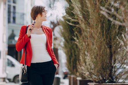 使用するおしゃれで健康的な電子タバコの外壮大な若いブルネット