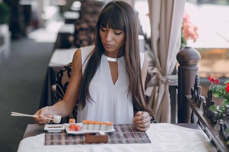 girl alone: beautiful girl enjoying sushi in a cafe on a sunny day Stock Photo