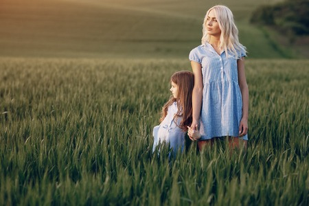 mom and daughter in beautiful dresses walk in field of beautiful summer weather