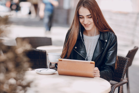 mooi blauw-eyed meisje in een cafe met tablet
