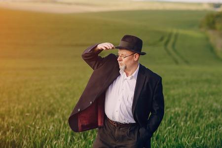 an elderly man walks on the field Stock Photo