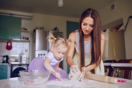 teaches: young beautiful mother teaches daughter prepare baking in the kitchen