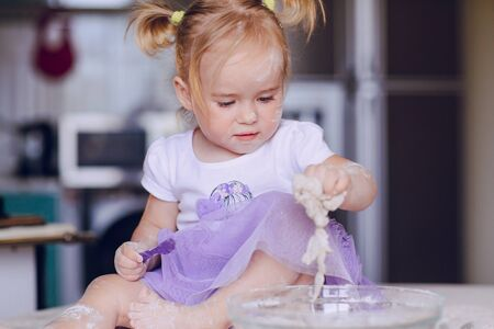 learns: beautiful little girl learns to cook a meal in the kitchen