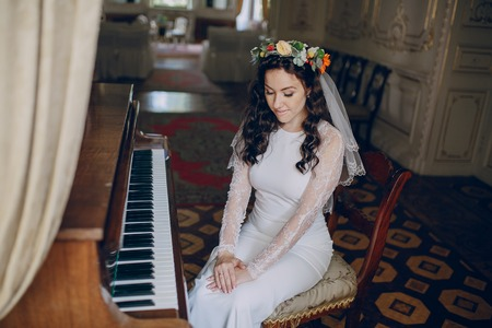 charming wedding couple playing on an old piano in the room