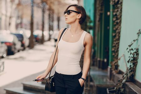 spectacular young brunette outside uses fashionable and healthy e-cigarette Stock Photo