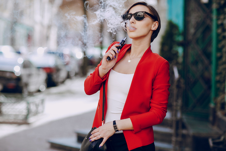 uses: spectacular young brunette outside uses fashionable and healthy e-cigarette Stock Photo