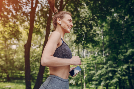 mp3 player: athletic girl running in the Park and doing exercises Jogging Stock Photo