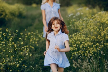 runing: mom and daughter in beautiful dresses walk in field of beautiful summer weather