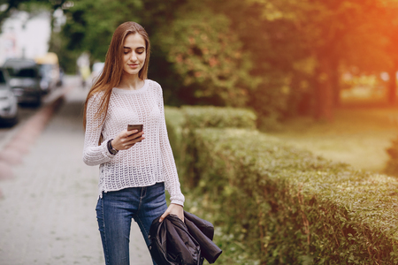 beautiful girl on the street using cell phones, a tablet and walks Zdjęcie Seryjne - 66287100