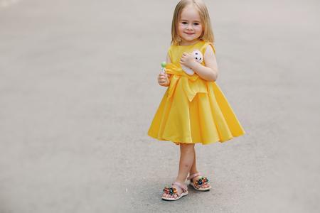 little beautiful girl walks through the city in  yellow dress