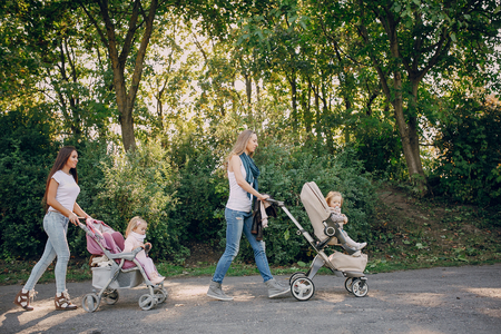 perambulator: young mother walking with her baby and carries it in a beautiful pram