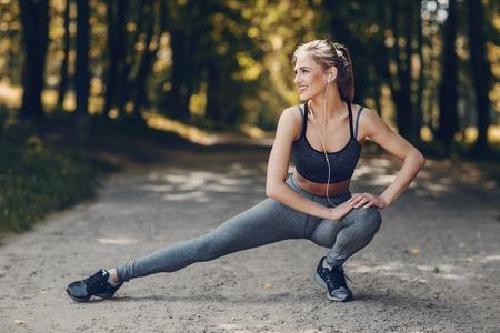 atletisch meisje loopt in het park en doet oefeningen Joggen