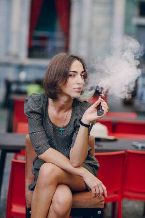 レストランの夏のテラスで美しいブルネット煙電子タバコ