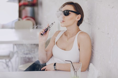 spectacular young brunette enjoys fashion and healthy electronic cigarette Stock Photo