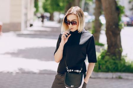 young beautiful girl enjoys electronic cigarette Standard-Bild