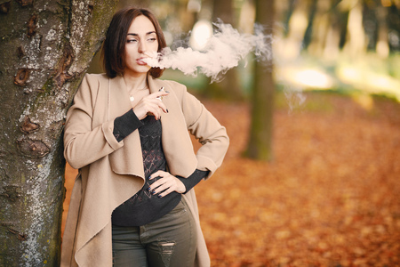 A girl smoking in the autumn park Stock Photo